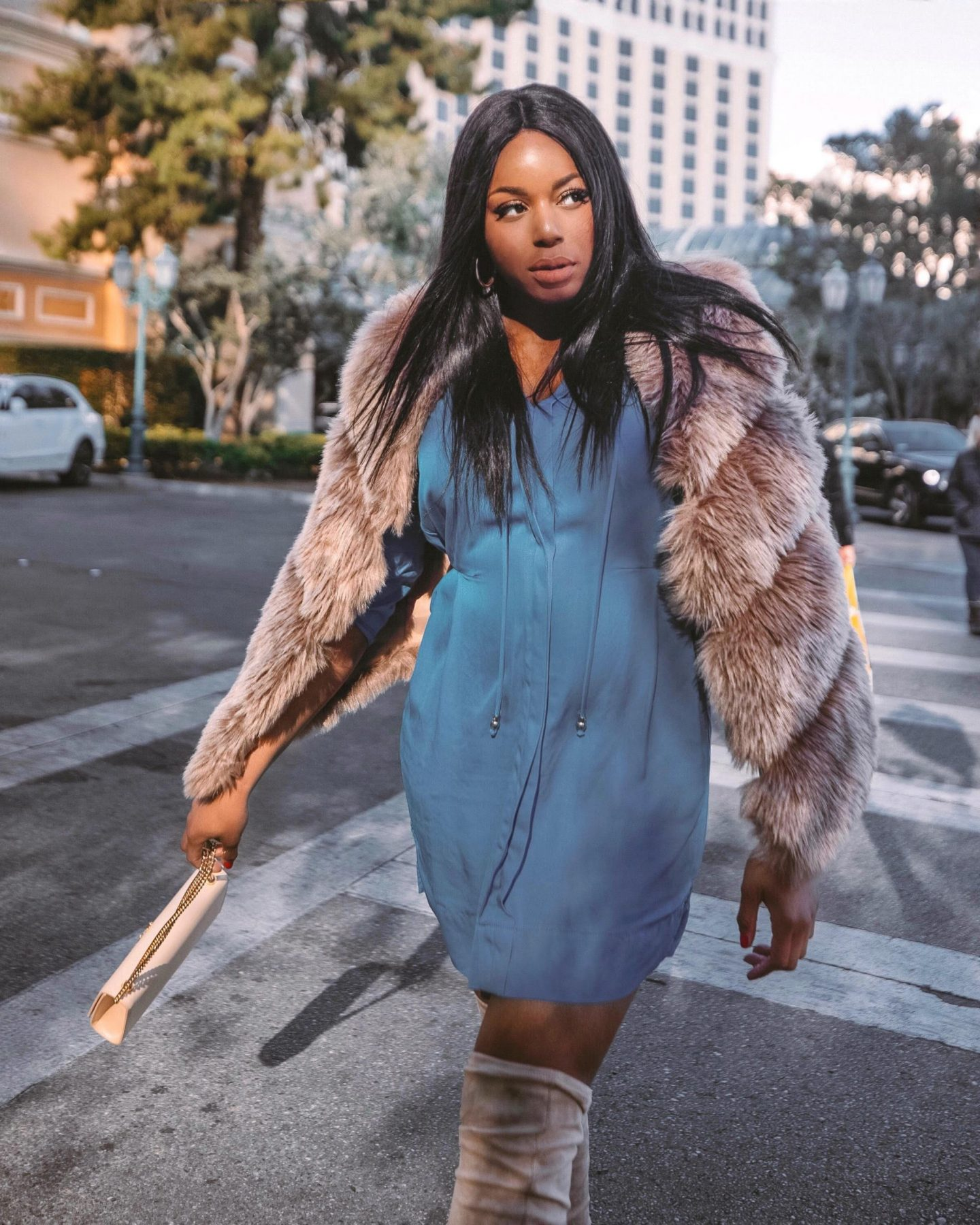 Fashion Influencer Kaye Bassey wearing a Faux Fur Vest + Blue DVF Dress in Vegas