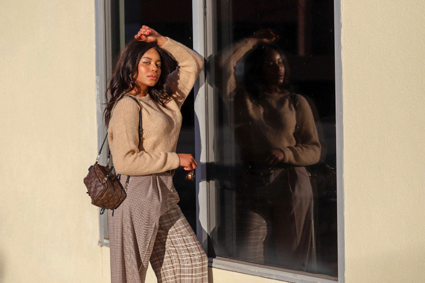 Influencer, Kaye Bassey, in a neutral, unique outfit featuring a beige sweater and plaid pants.
