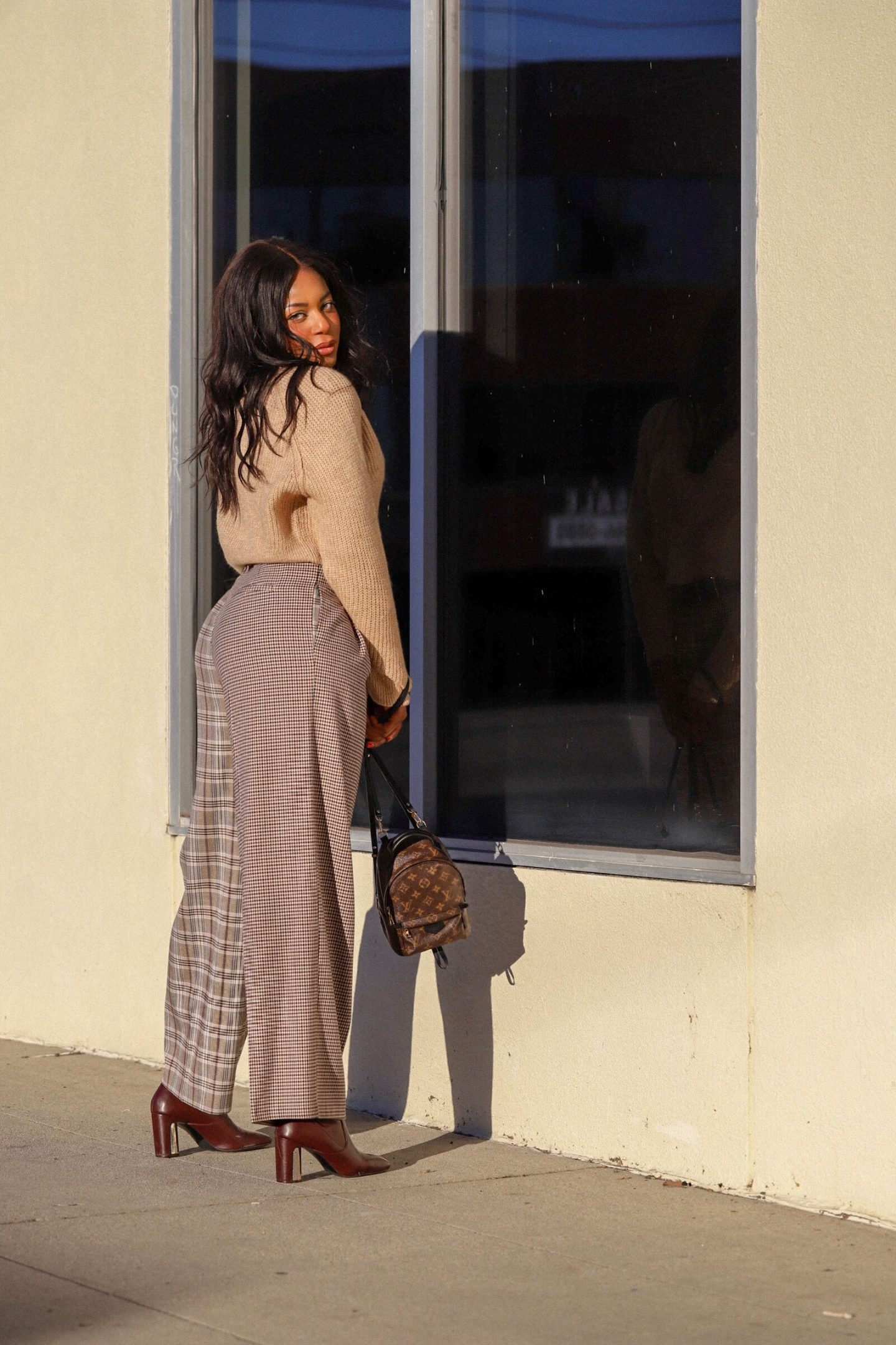 Kaye Bassey, an influencer, modeling a fall look from Nordstrom featuring a beige sweater and plaid pants.