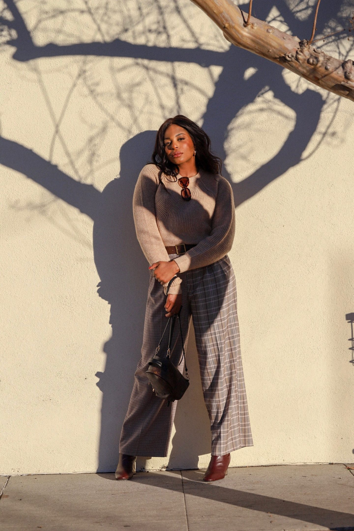 Kaye Bassey posing in front of a wall to showcase a unique outfit for the fall.