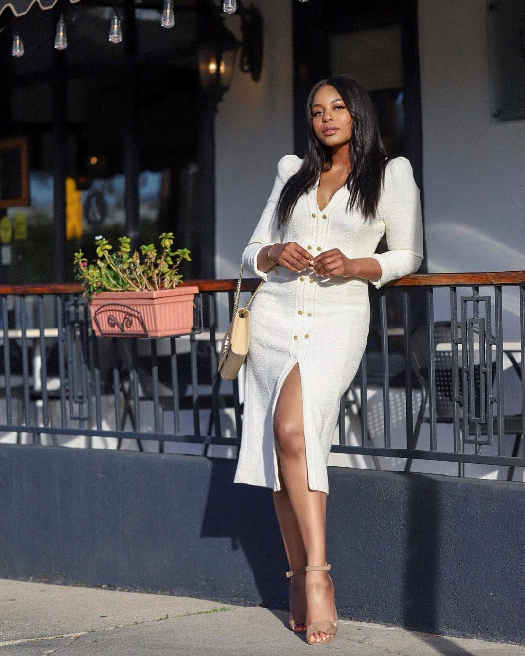 Kaye Bassey in white midi dress and heels outside of a restaurant