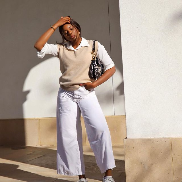 Kaye Bassey in neutral sweater vest and white jeans