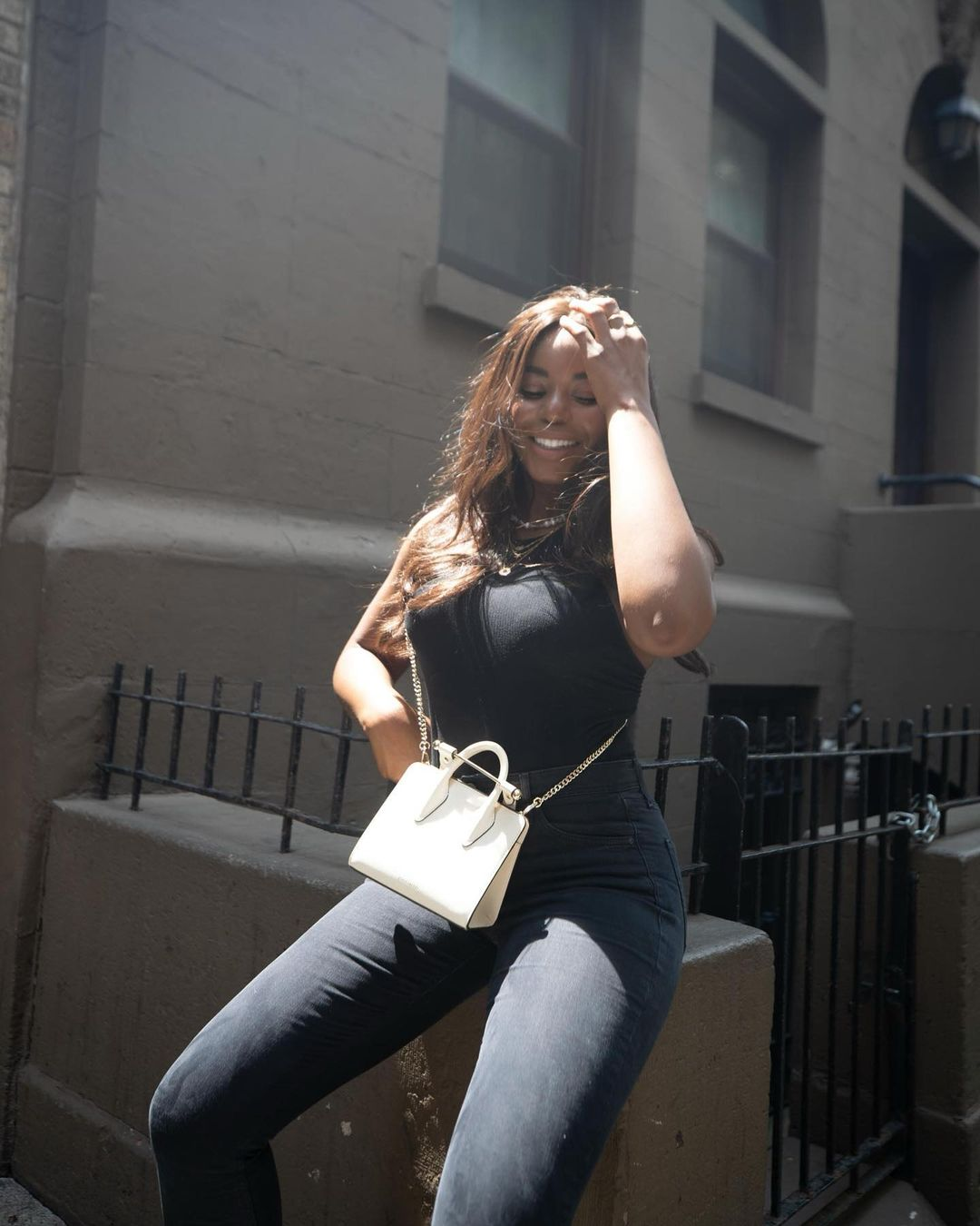 Model, Kaye Bassey, in a black sleeveless top, grey skinny jeans with a white tote bag - street style photography