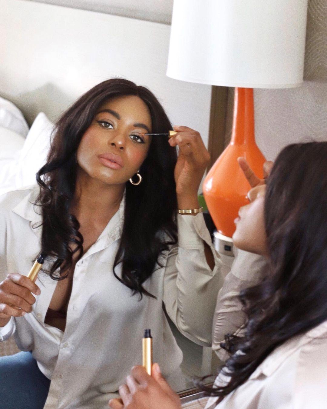 Kaye Bassey in mirror applying mascara to eye in silk blouse