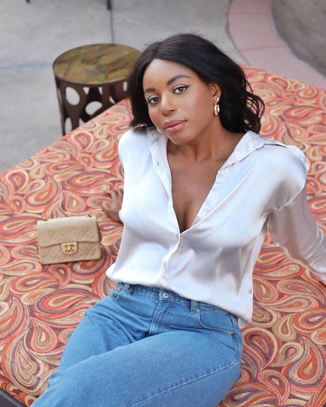 Kaye Bassey in silk blouse, light denim jeans and Chanel purse. Wearing Amazon beauty products