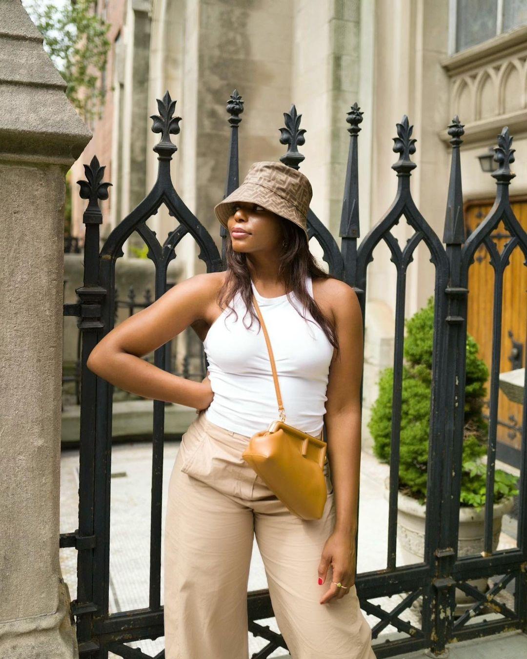 Wearing Fendi logo bucket hat, white racerback tank top, khaki wide leg pants and Fendi mustard handbag.