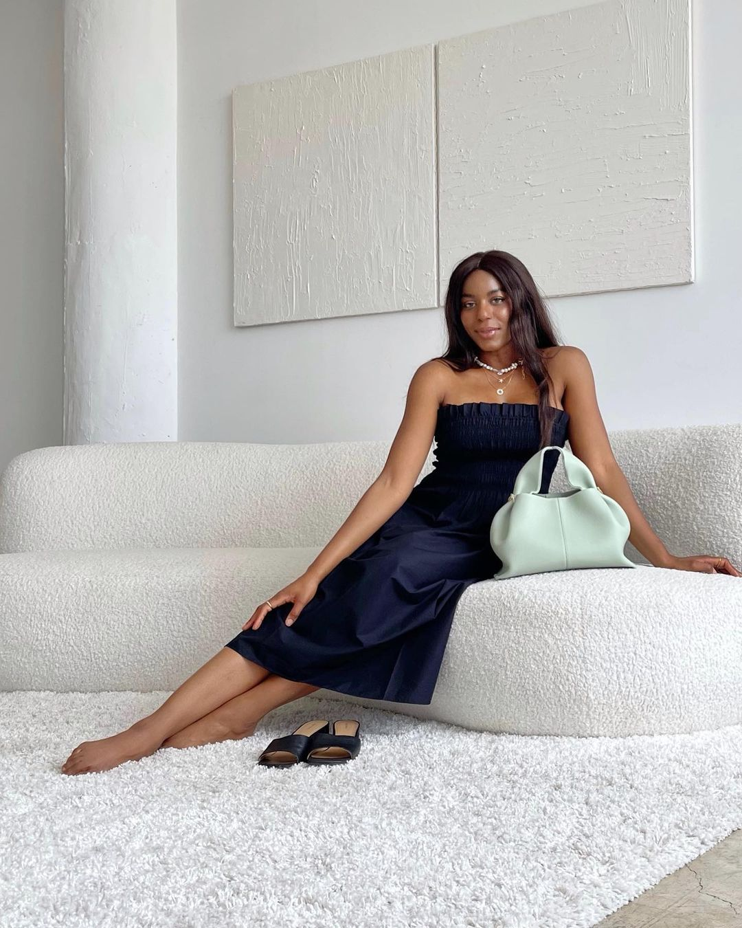 Kaye Bassey in navy midi dress sitting on a boucle curved sofa with a mint handbag
