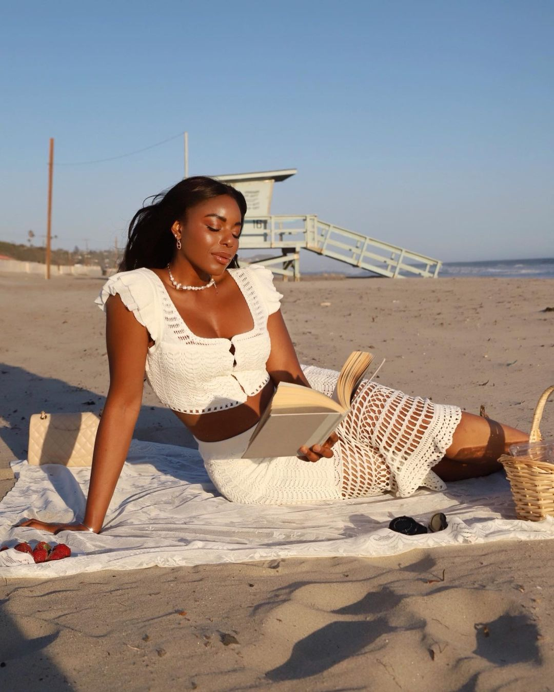 Kaye Bassey in matching crochet set. Reading a book while on the beach. Labor Day Outfit Ideas