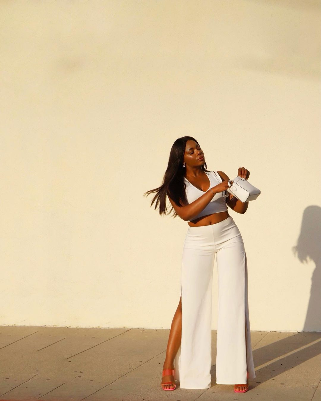 Model wearing a white monochrome outfit - crop tank and wide leg pants - Labor Day Outfit Ideas