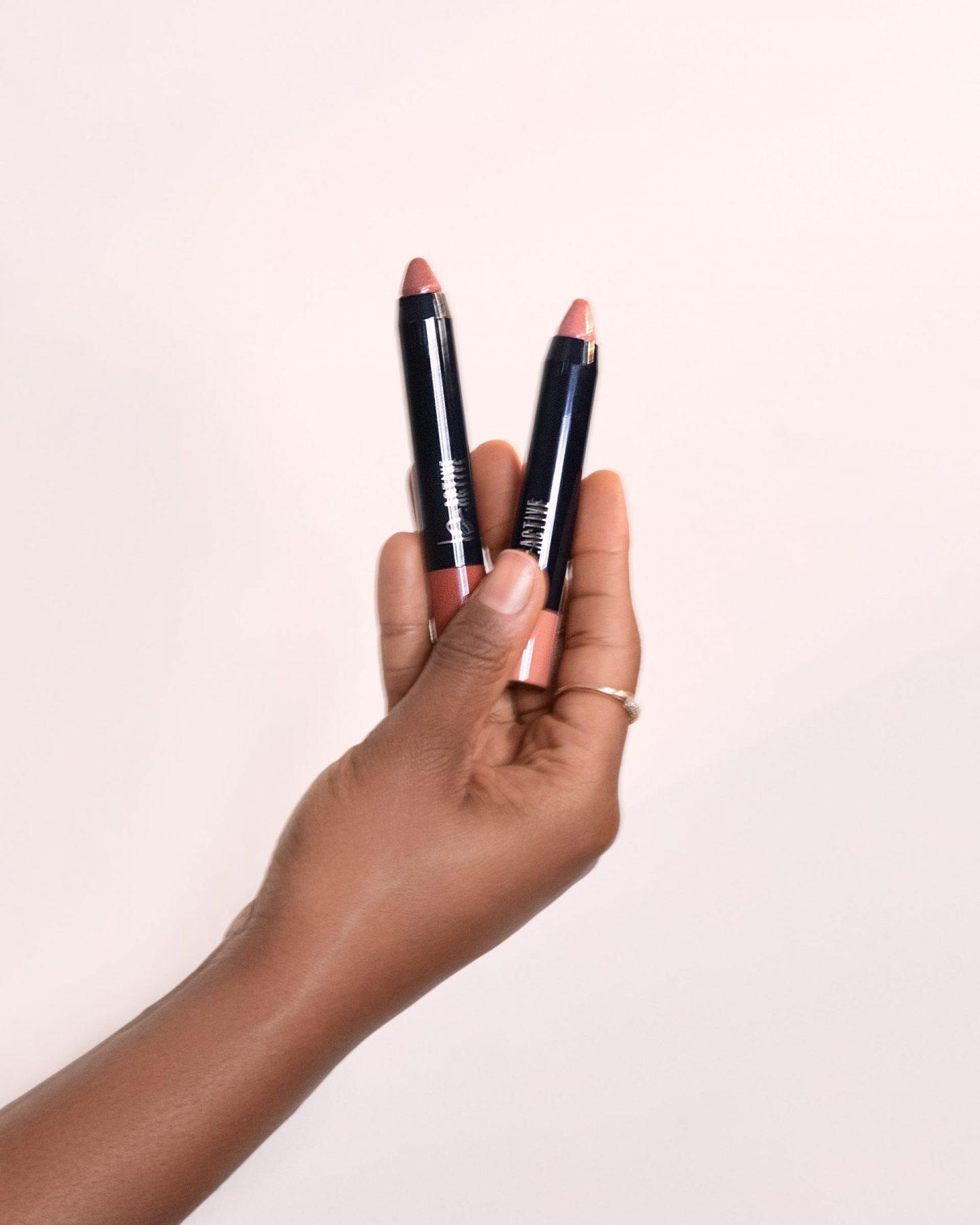 Kaye Bassey holding One Click Beauty matte lip crayon and sheer lip crayon - perfect nudes beauty kit