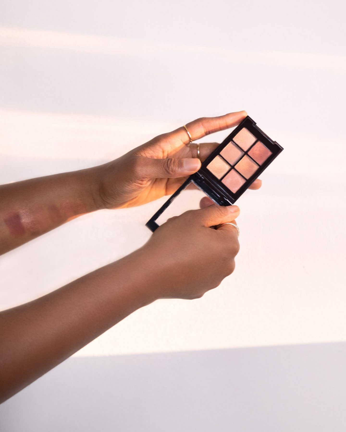 One Click Beauty Perfect Nudes eyeshadow palette being held by influencer, Kaye Bassey