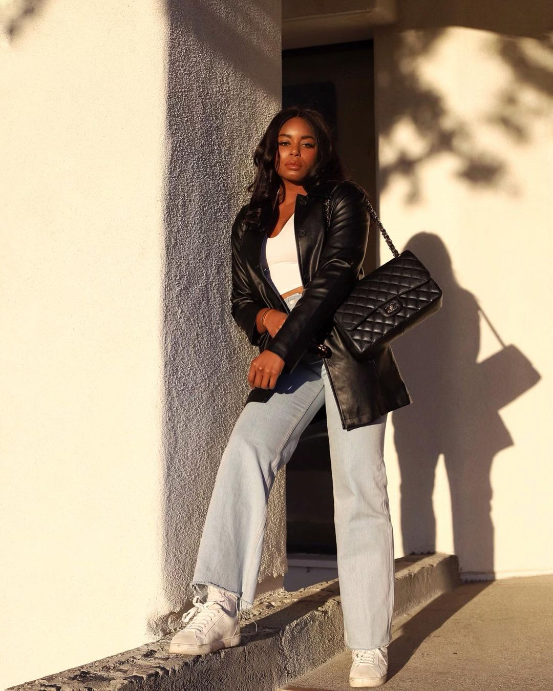 Faux-leather blazer, white cropped racerback tank top, light wash straight leg denim, white tennis sneakers and Chanel classic flap quilted bag - Stores like Zara outfit