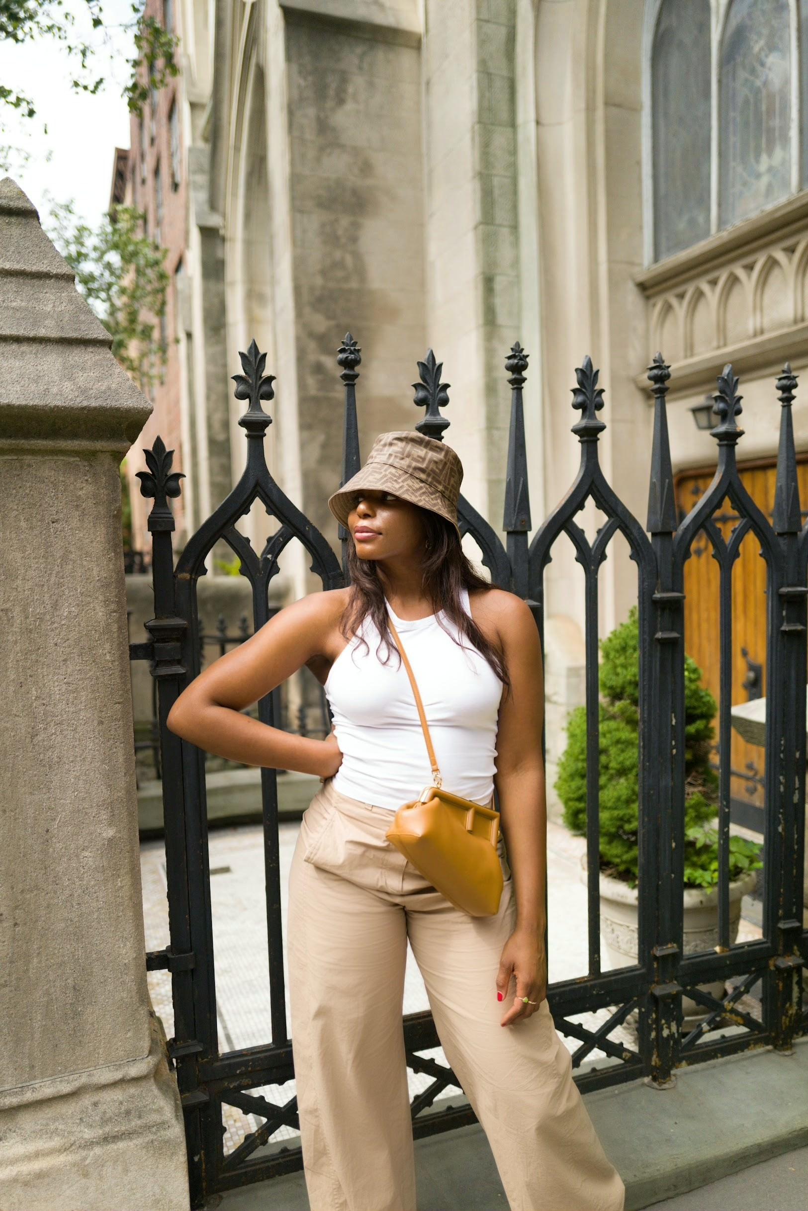 Influencer, Kaye Bassey, in a street style fashion photo wearing a Fendi bucket hat, white tank, wide leg pants and Fendi First handbag.