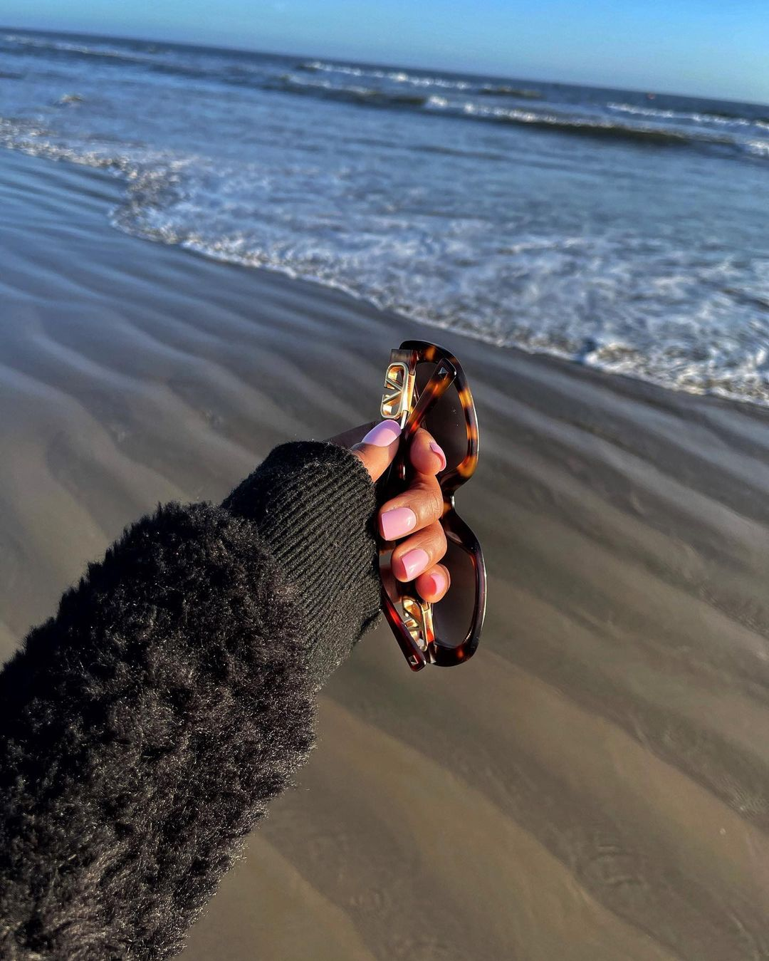 Purple press on nails while holding glasses at the beach